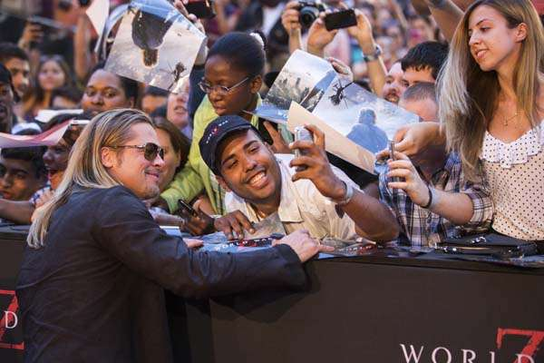 "Cast member and producer Brad Pitt poses with a fan for a photo as he arrives for the premiere of the film ""World War Z"" in New York"