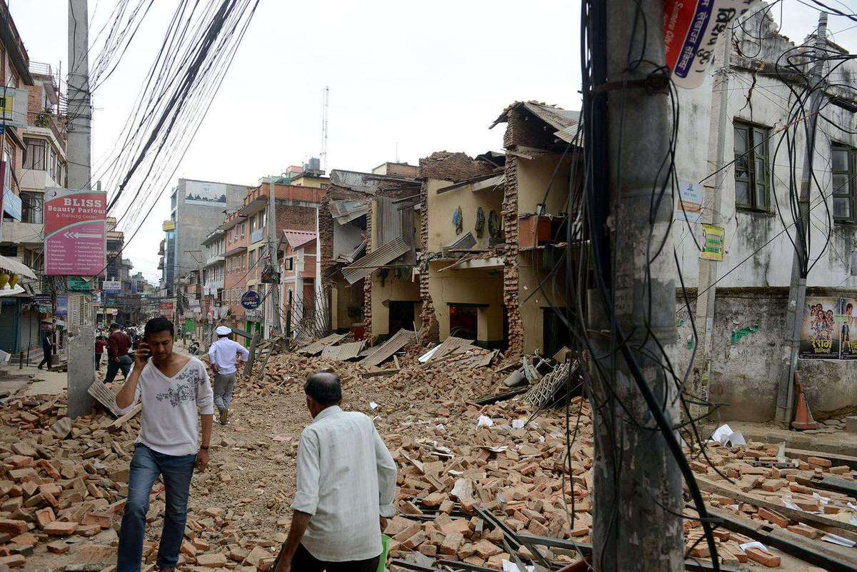Nepalese people walk past collapsed buildings