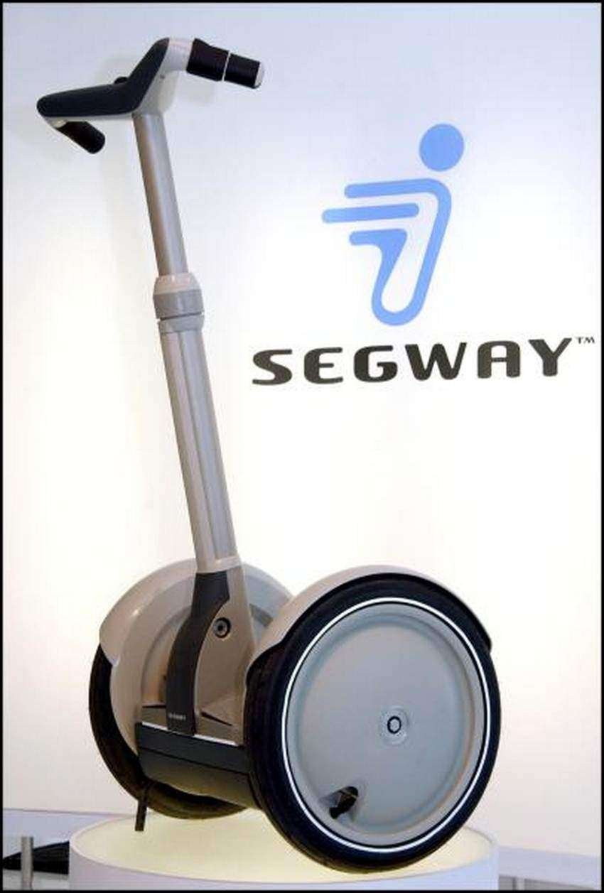 "UNITED STATES - DECEMBER 03: Inventor Dean Kamen presents the ""Segway Human Transporter"" in New York, United States on December 03, 2001 - The Segway is the first self-balancing electric powered transportation machine - The Segway will be introduced for commercial use in 2002, and for consumers at the end of that year - The Segway, better known by its former code name, Ginger, can go up to 12 miles an hour and has no brakes - It's speed and direction are controlled solely by the rider's shifting weight and a manual turning mechanism on one of the handle bars. (Photo by David LEFRANC/Gamma-Rapho via Getty Images)"