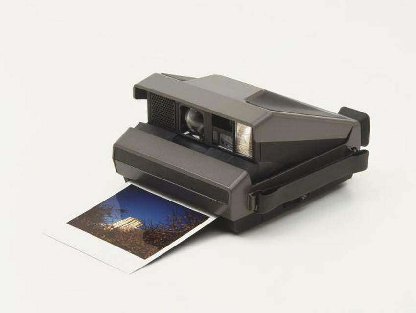 Polaroid camera with photographic print ejected from paper slot, close up