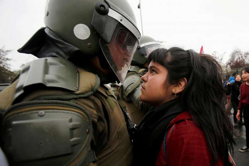 A demonstrator looks at a riot policeman during a protest marking the country's 1973 military coup in Santiago, Chile September 11, 2016. REUTERS/Carlos Vera
