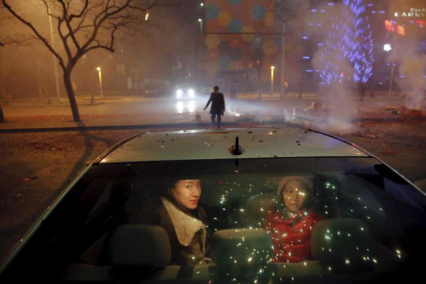 A girl and a woman sit inside the car as firecrackers and fireworks explode celebrating the start of the Chinese Lunar New Year of Monkey in Beijing just before midnight February 7, 2016. REUTERS/Damir Sagolj