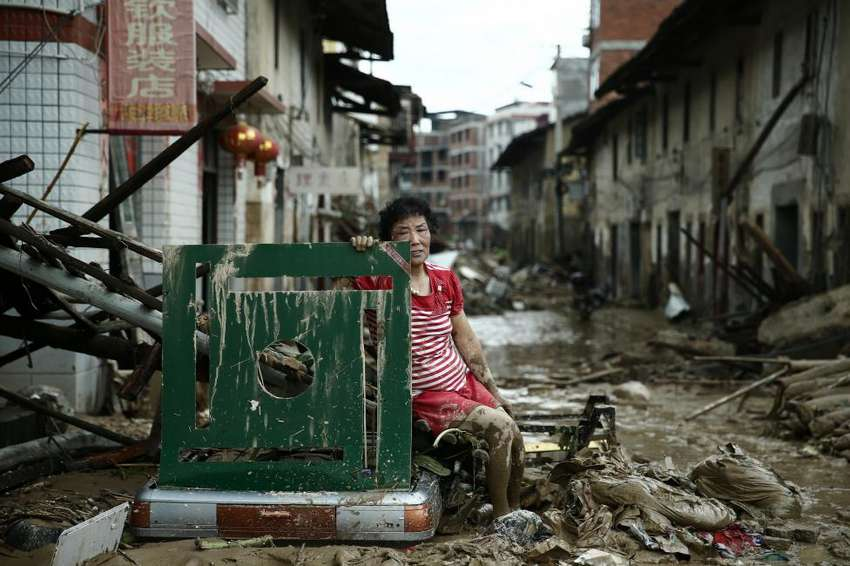 A woman sits on the ruins after typhoon Nepartak swept through Minqing county, Fujian province, China, July 10, 2016. Picture taken July 10, 2016. REUTERS/Stringer REUTERS ATTENTION EDITORS - THIS IMAGE WAS PROVIDED BY A THIRD PARTY. EDITORIAL USE ONLY. CHINA OUT. NO COMMERCIAL OR EDITORIAL SALES IN CHINA. TPX IMAGES OF THE DAY