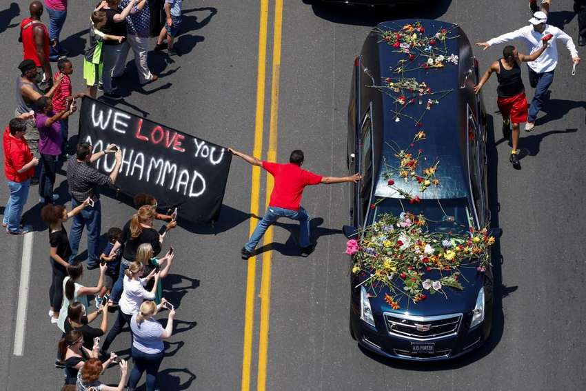 "A banner stating ""We Love You Muhammad"" is displayed as well-wishers touch the hearse carrying the body of the late boxing champion Muhammad Ali during his funeral procession through Louisville, Kentucky, June 10, 2016. REUTERS/Adrees Latif"