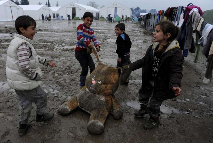 Refugee children play with a stuffed toy at a muddy makeshift camp at the Greek-Macedonian border, near the village of Idomeni, Greece March 15, 2016. REUTERS/Alexandros Avramidis